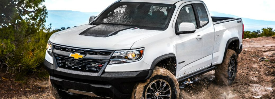 white chevy colorado driving through the mud