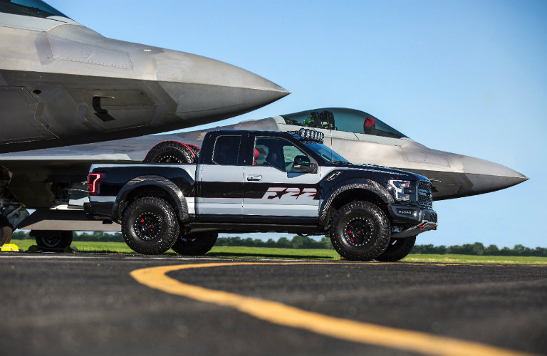 side view of the U.S. Air Force High Performance F-22 F-150 Raptor parked between two F-22 fighter jets
