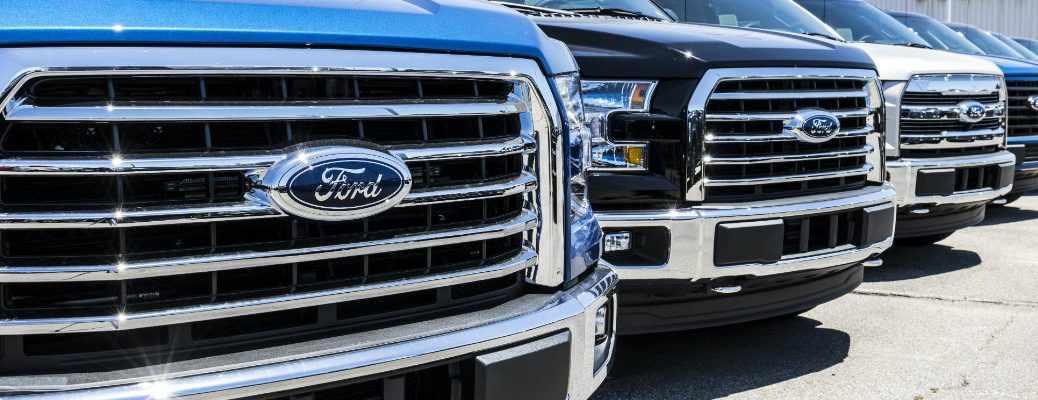 Front grilles of Ford F-150 trucks in line at dealership