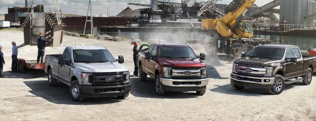 Three Ford Super Duty trucks lined up side by side on worksite