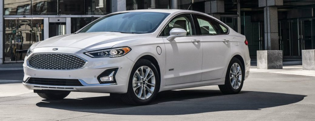 Profile view of white 2019 Ford Fusion Hybrid parked in front of building in daytime