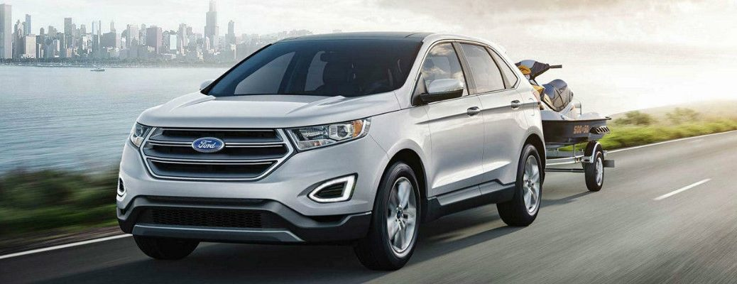 White 2018 Ford Edge driving down waterfront road with trailer in tow