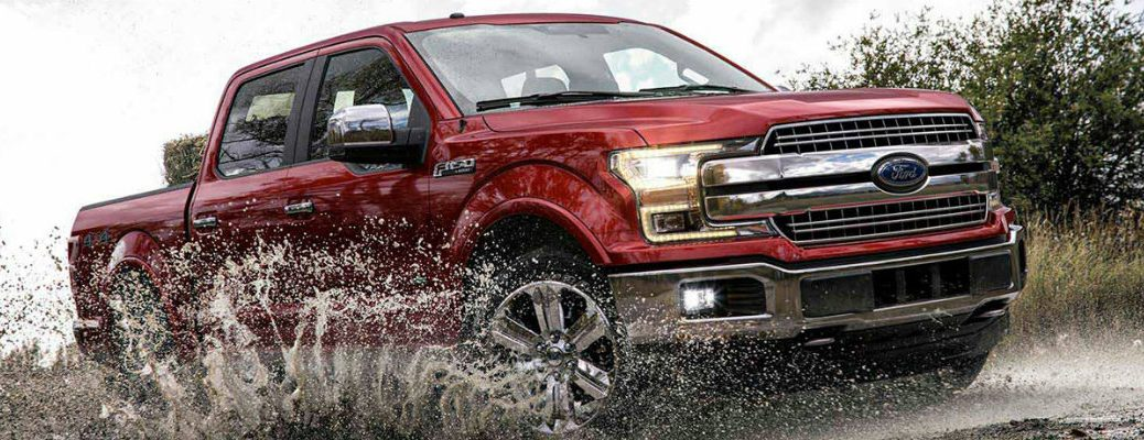 Red 2018 Ford F-150 driving through mud