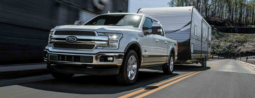 White 2018 Ford F-150 King Ranch towing camper on two-lane road