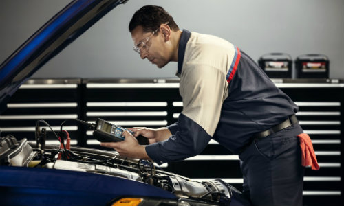 Ford mechanic checking battery level prior to replacement