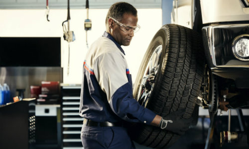 Mechanic at Ford dealership installing new tire