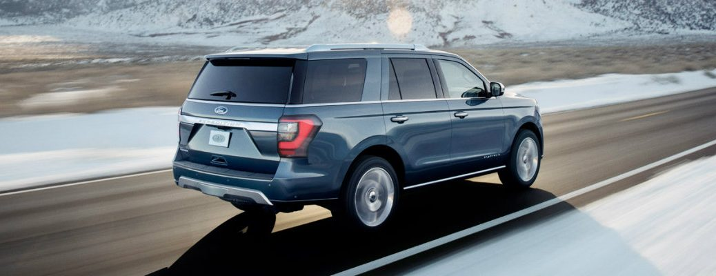 Rear view of blue 2018 Ford Expedition driving on snowy and mountainous road