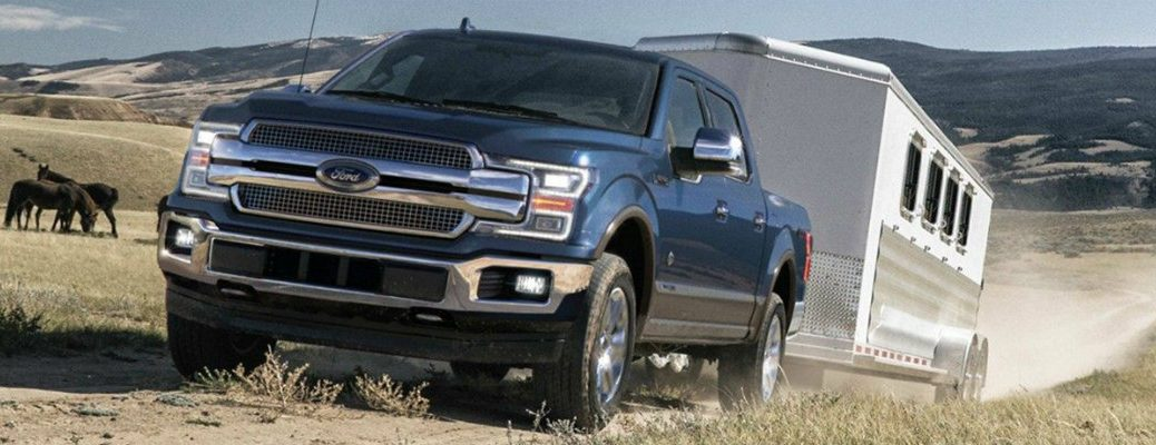 Blue 2019 Ford F-150 towing trailer through ranch with horses in background