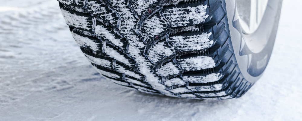 Isolated view of winter tire treads digging through snow