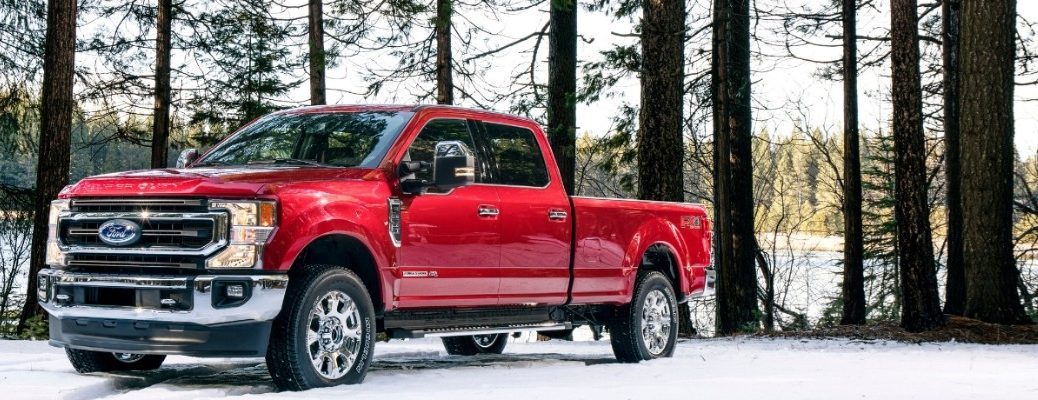 Red 2020 Ford Super Duty parked on snowy terrain with trees in background