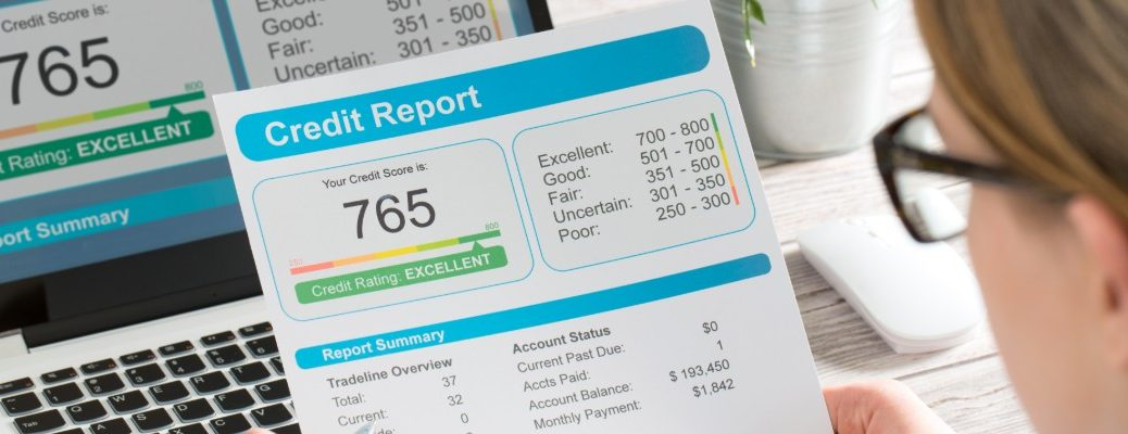 Woman looking at sheet displaying credit score and report