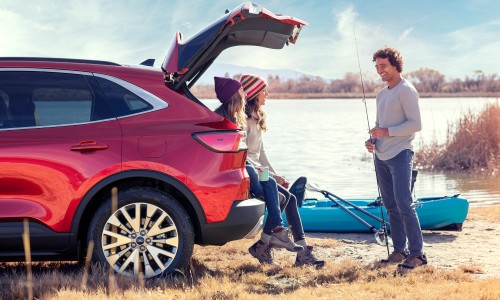 Two people loading cargo in rear of 2020 Ford Escape