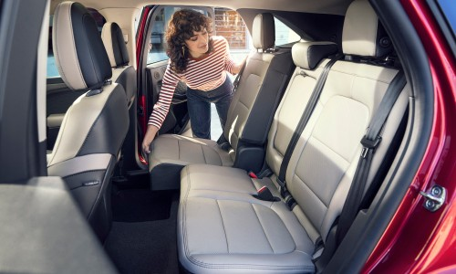 Woman folding up second row of seats inside 2020 Ford Escape