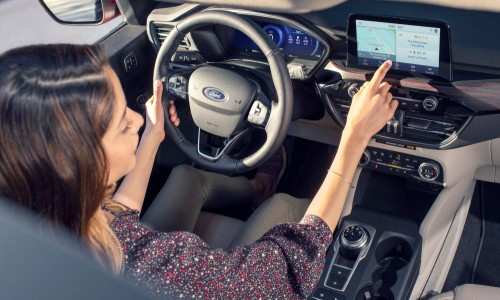Woman operating centre touchscreen inside 2020 Ford Escape