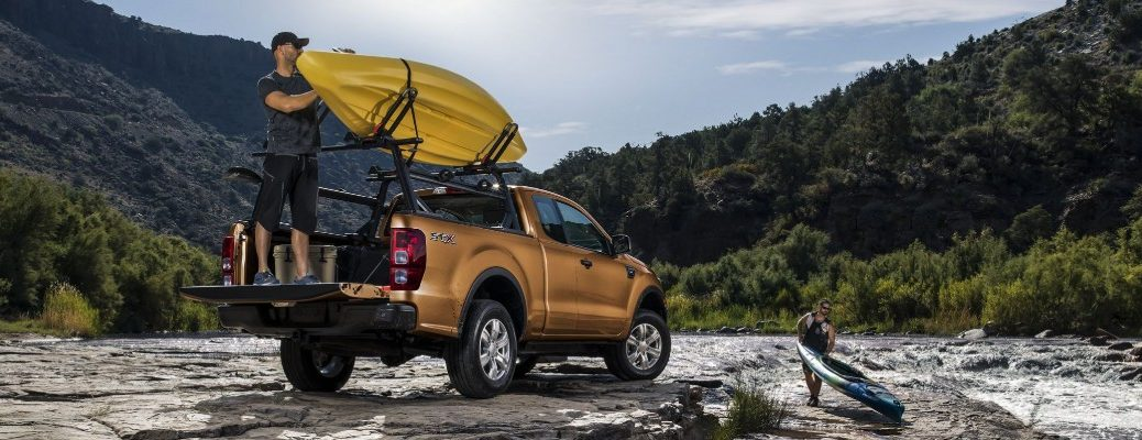 Man loading boat in rear cargo area of 2019 Ford Ranger