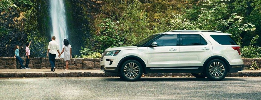 White 2019 Ford Explorer parked in front of waterfall with people looking on