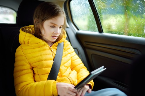 Young girl playing on phone inside vehicle