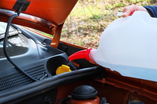 Man pouring windshield washer fluid in receptacle