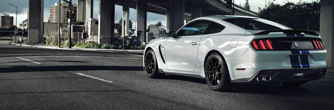 White 2019 Ford Mustang Shelby GT350 driving on road under bridge