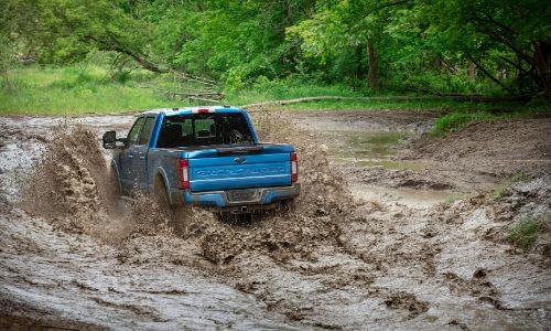 Rear view of 2020 Ford Super Duty Tremor Package driving through muddy terrain