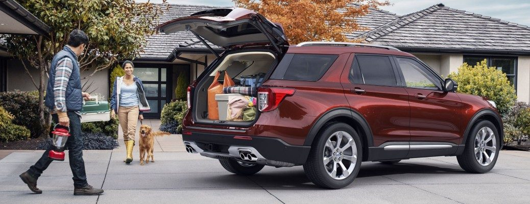 People loading cargo in rear area of red 2020 Ford Explorer
