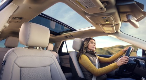 Woman driving in 2020 Ford Explorer with panoramic sunroof in frame