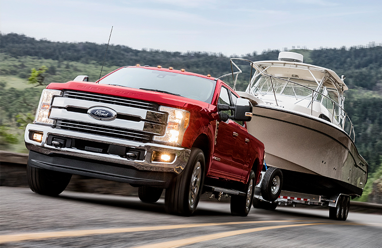 Red Ford Super Duty towing boat on highway
