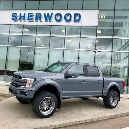 Custom F-150 in front of Sherwood Ford facade