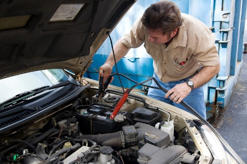 Man checking vehicle battery inside mechanic shop