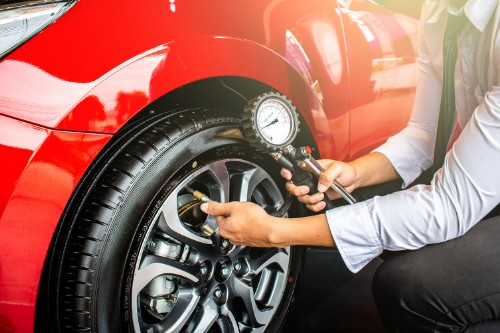 Young professional checking tire pressure