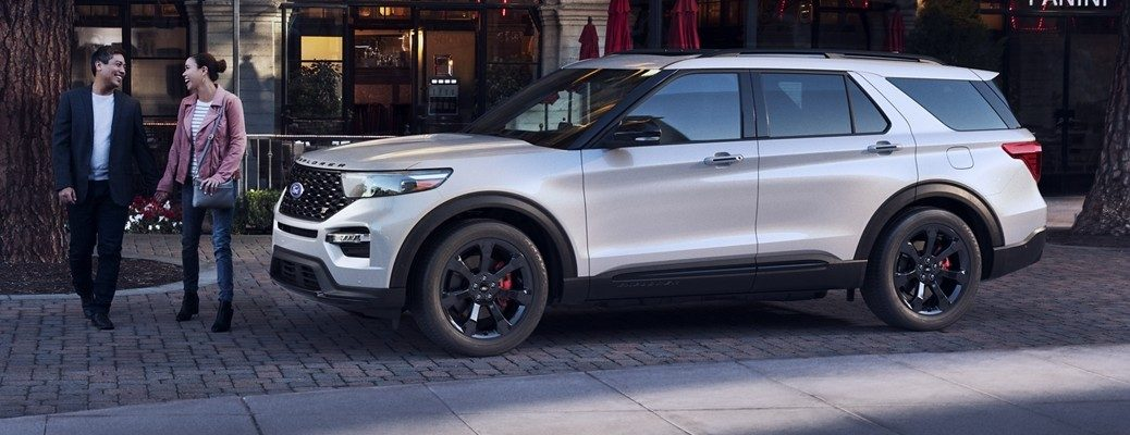 Two people walking in front of white 2020 Ford Explorer