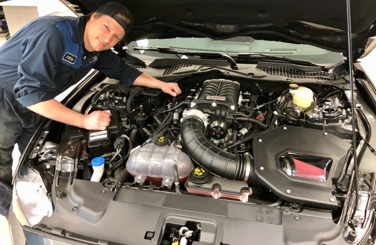 Sherwood Ford service team member posing with supercharged Mustang GT engine