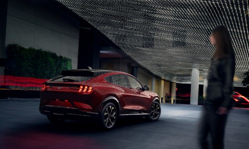 Woman walking towards red 2021 Ford Mustang Mach-E