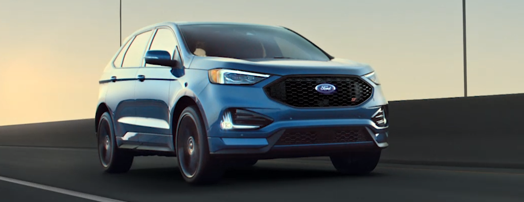 Front view of 2020 Ford Edge driving on highway road at sundown