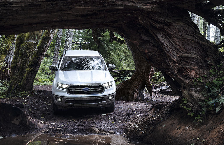 Front view of white 2020 Ford Ranger driving through woods