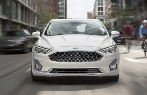 Front view of white 2020 Ford Fusion driving through city