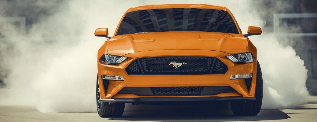 Front view of orange 2020 Ford Mustang GT500 burning rubber on track