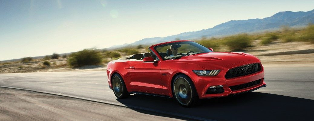 Red 2017 Ford Mustang convertible driving on desert road