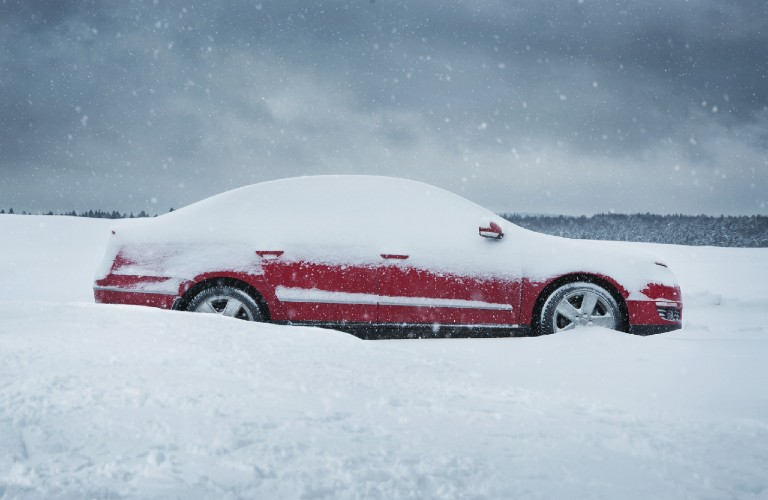 red car in deep snow