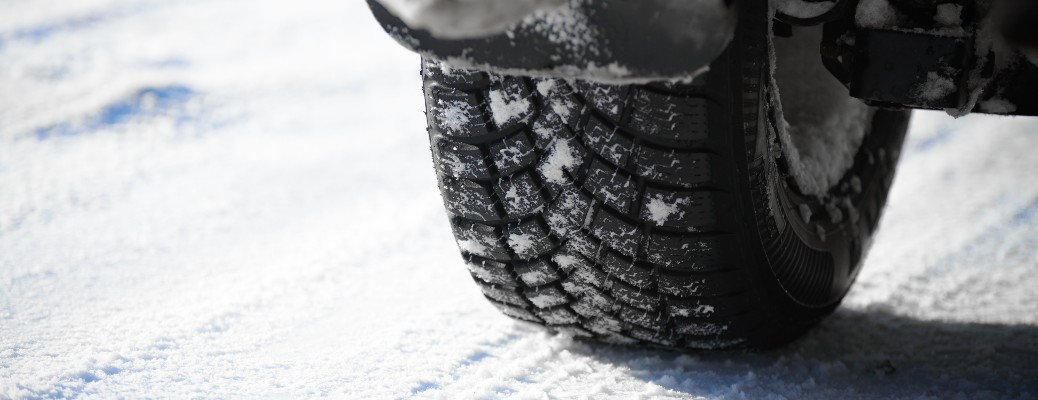 close up of a winter tire on a snowy road