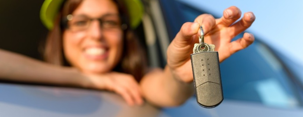 a happy woman holding a car key FOB