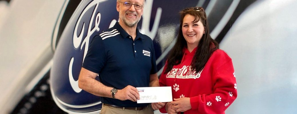 David from Sherwood Ford and SCARS representative holding donation check