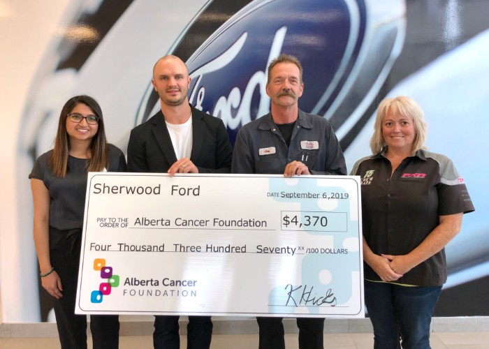 Kurtis from Sherwood Ford holding cheque with members of Alberta Cancer Foundation