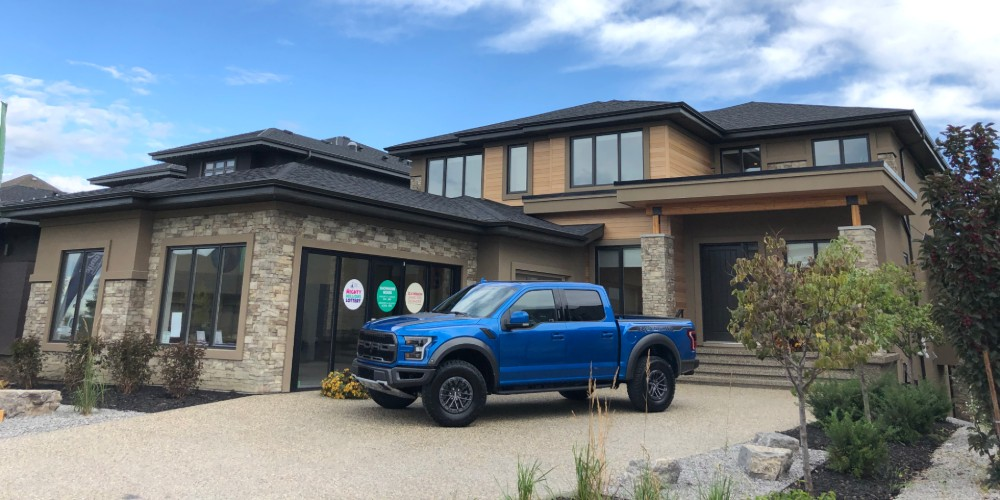 Blue Ford Raptor parked in front of new house