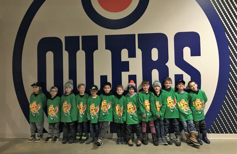 Golden Gophers team posing in front of Edmonton Oilers logo