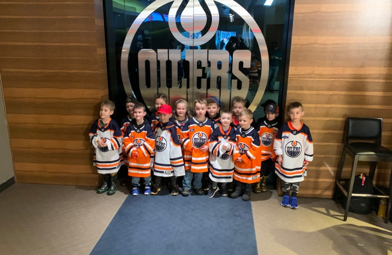 Red Devils youth hockey club posing in front of Oilers logo