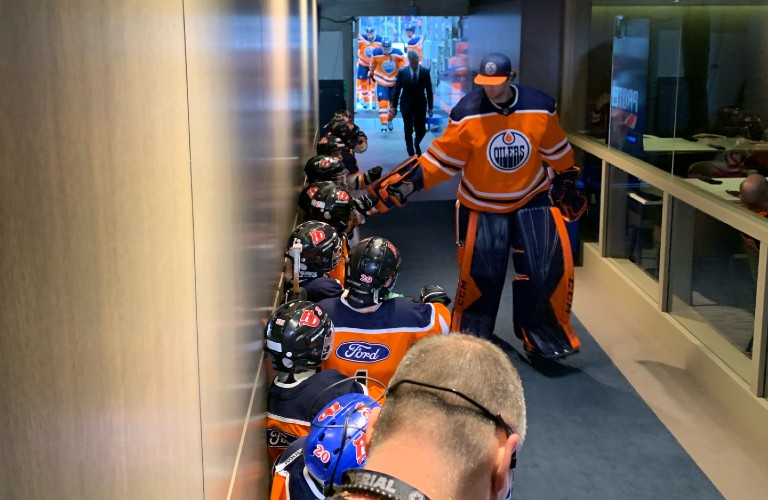 Red Devils hockey team in Rogers Place tunnel meeting Oilers players