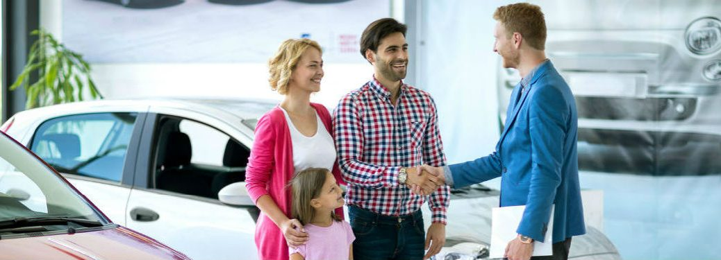 Family making deal with car dealer for new car