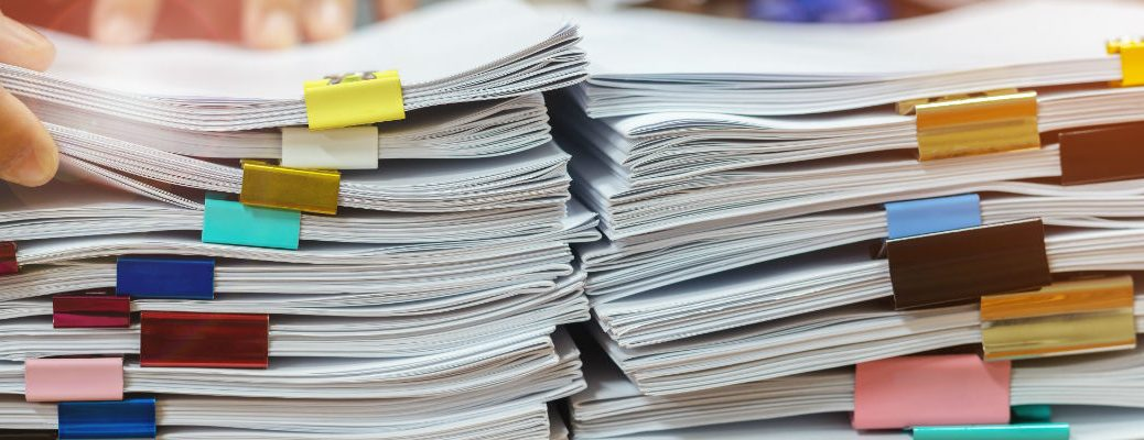 A stock photo of a stacks of paperwork on a desk.