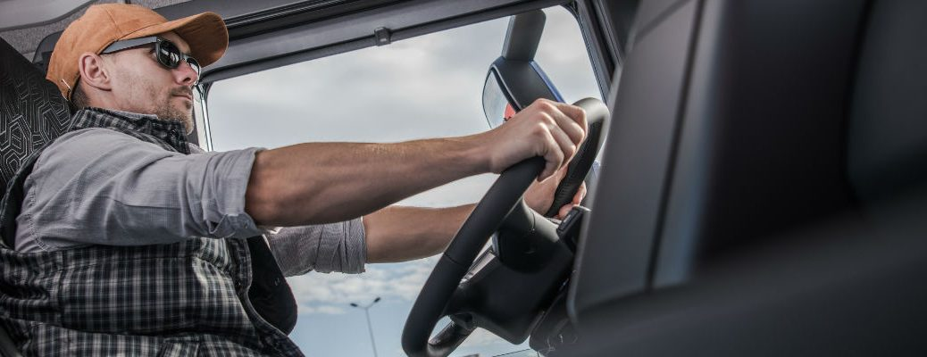 A stock photo of a truck driver behind the wheel of a semi.